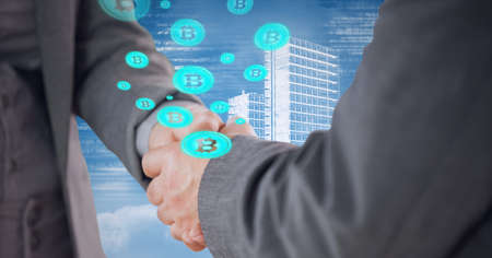 Composition of businessmen shaking hands with bitcoin symbols over modern office buildings. global business, finances and networking concept digitally generated image. Standard-Bild