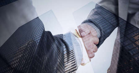 Composition of businessmen shaking hands over modern office buildings. global business, finances and networking concept digitally generated image.