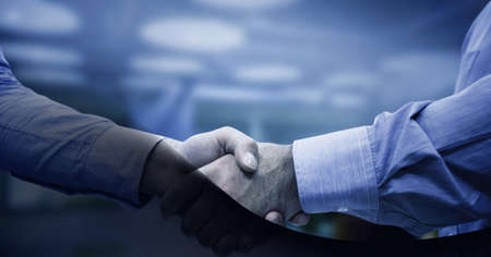 Black technology background over mid section of two businessmen shaking hands against cityscape. global business and technology concept