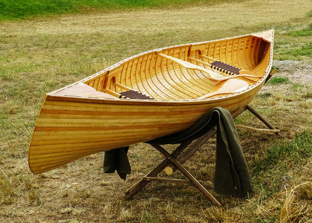 Wooden boat placed on a wooden stand in the meadow.After the boat and over the stand there is a blanket.In the boat there are two rowing boats and two knit benches.The boat is new.Friendly for the background.