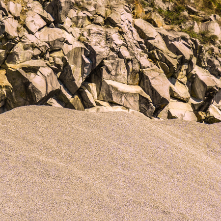 Pile of sand and sharp rock with little vegetation