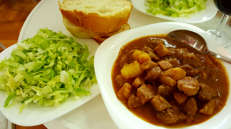 Served juicy goulash with fresh green salad and bread. White plates on a white table. A glass of wine next to a plate Imagens