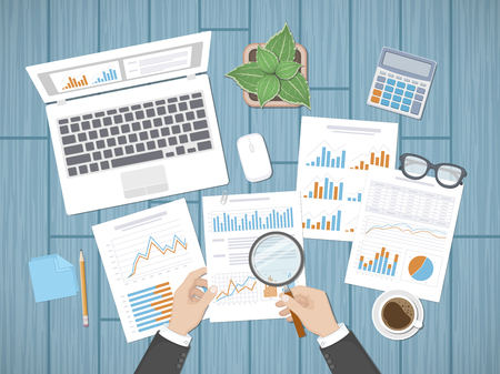 Auditing concepts. Businessman auditor inspects assessing financial documents. Man's hands with magnifying glass above graphics and charts. Research, management, planning, accounting, analysis, data.
