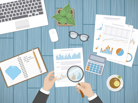 auditing: Auditing concepts. Businessman auditor inspects assessing financial documents. Mans hands with magnifying glass above graphics and charts. Research, management, analysis, data, planning, accounting