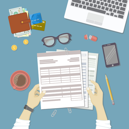 tax form: Man working with documents. Human hands hold the accounts, bills, tax form. Workplace with papers, blanks, forms, phone, wallet with money, credit cards, glasses, coins, leptop coffee. Top view Vector