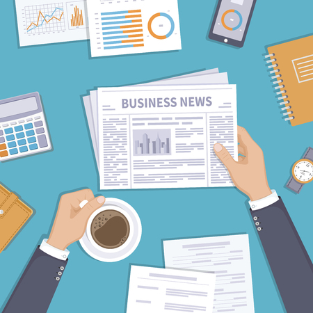 Business news. Businessman holding a newspaper and coffee cup on the desktop. Coffee break, breakfast, lunch, documents, purse, calculator, notebook, wrist watch. View from above