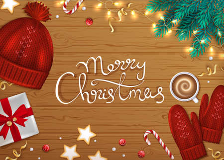 Merry Christmas and Happy New Year Greeting Background. Hand Drawn Lettering. Winter Elements fir branches, knitted hat, mittens, coffee, gift, cookies, ribbons on a wooden table. Top View.