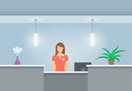 Young woman receptionist stands at reception desk