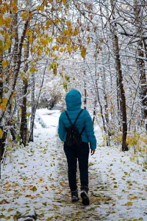 A girl in a blue down-padded jacket with a black backpack on the background of the winter alley. Trekking walks in the snowy forest.