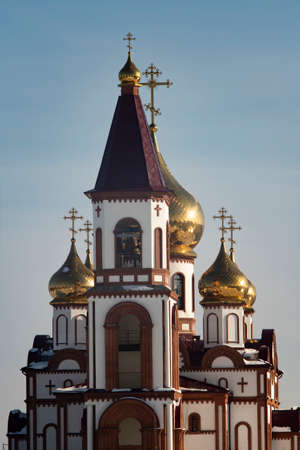 Church against the blue sky. White church with a red conical roof. Church with golden domes and crosses.