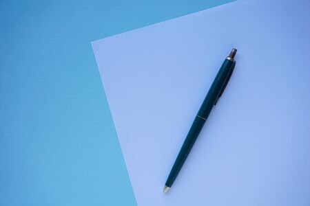 pen lies on white paper with blue surface. Office Minimalism Concept background. Flat lay