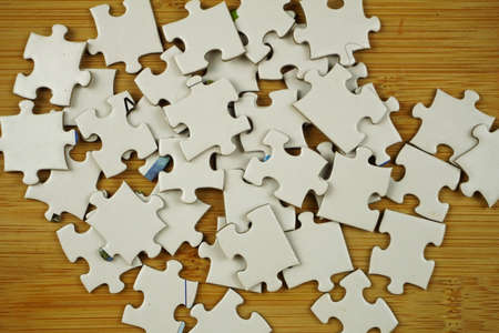 random jigsaw puzzle incomplete concept on wooden background. Copy space for text