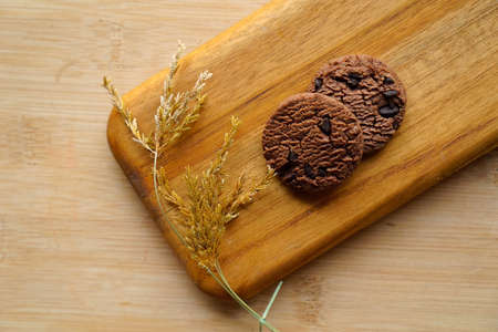 chocolate cookies and dark chocolate grain on wooden board background. for text concept advertising