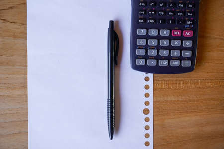 blank paper, ballpoint, and calculator for mockup concept on wooden board. finance, education background Banco de Imagens - 154877573