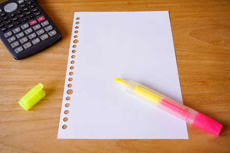 blank paper, ballpoint, and calculator for mockup concept on wooden board. finance, education background Banco de Imagens