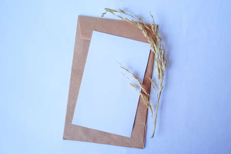 Brown envelope and white letter with dried grass for mockup greeting seasonal concepts