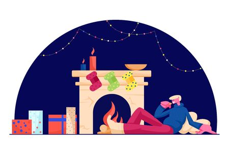 Relaxed Man in Warm Cozy Sweater Sitting on Pillows at Fireplace with Hanging Socks, Burning Candle and Many Gift Boxes
