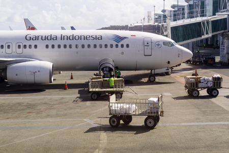 BALIKPAPAN, INDONESIA - AUGUST 02, 2017 : Ground staff loading pasangger baggage and cargo to Garuda Indonesia Boeing 737-800NG cargo hold at Sultan Aji Muhammad Sulaiman Airport Sepinggan Balikpapan. Garuda Indonesia is national airline of Indonesia.