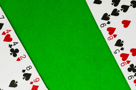 Playing or poker cards on green background with copy space. Stock Photo