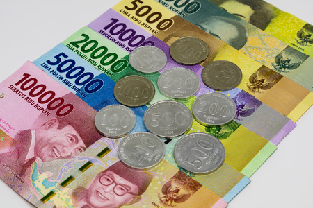 Closeup shot of Indonesia Rupiah banknotes and coins in white background. Stock Photo