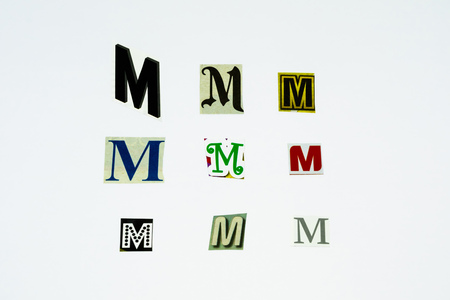 Set of collection colorful newspaper cut out letters as ornaments or design elements. Isolated on white background. Letter M. Stock Photo