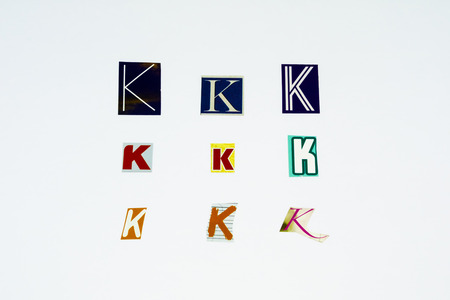 Set of collection colorful newspaper cut out letters as ornaments or design elements. Isolated on white background. Letter K. Stock Photo