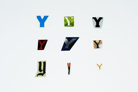 Set of collection colorful newspaper cut out letters as ornaments or design elements. Isolated on white background. Letter Y.
