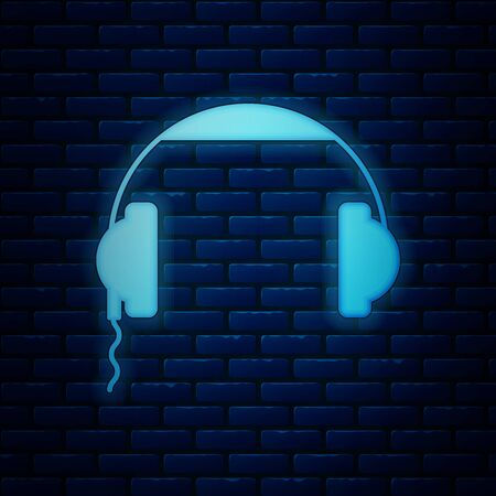 Glowing neon Headphones icon isolated on brick wall background. Earphones sign. Concept for listening to music, service, communication and operator. Vector Illustration