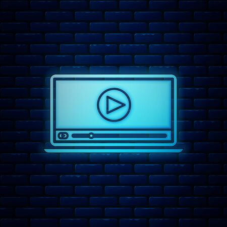 Glowing neon Online play video icon isolated on brick wall background. Laptop and film strip with play sign. Vector Illustration