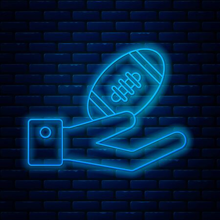 Glowing neon line American Football ball on hand icon isolated on brick wall background. Rugby ball icon. Team sport game symbol. Vector Illustration