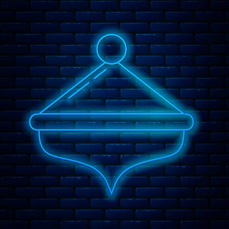 Glowing neon line Hanukkah dreidel icon isolated on brick wall background. Vector Illustration