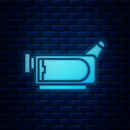 Glowing neon Cinema camera icon isolated on brick wall background. Video camera. Movie sign. Film projector.  Vector Illustration