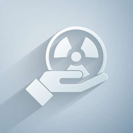 Paper cut Radioactive in hand icon isolated on grey background. Radioactive toxic symbol. Radiation Hazard sign. Paper art style. Vector