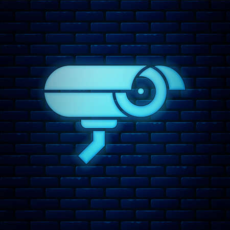 Glowing neon Security camera icon isolated on brick wall background. Vector