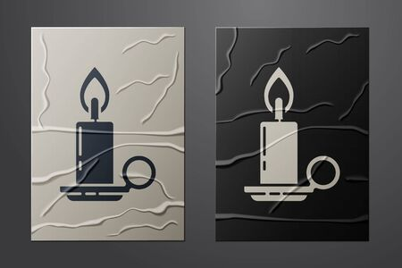 White Burning candle in candlestick icon isolated on crumpled paper background. Cylindrical candle stick with burning flame. Paper art style. Vector Vettoriali