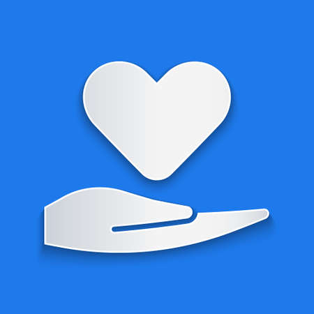 Paper cut Heart on hand icon isolated on blue background. Hand giving love symbol. Valentines day symbol. Paper art style. Vector Illustration.