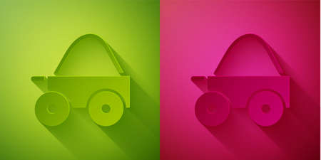 Paper cut Wooden four-wheel cart with hay icon isolated on green and pink background. Paper art style. Vector.