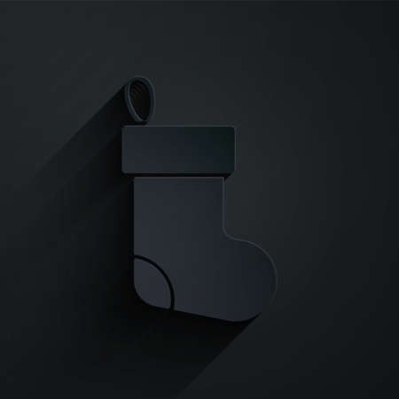 Paper cut Christmas stocking icon isolated on black background. Merry Christmas and Happy New Year. Paper art style. Vector