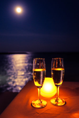 Romantic scene. Two glasses of champagne on the table with candle near the sea under moon light.