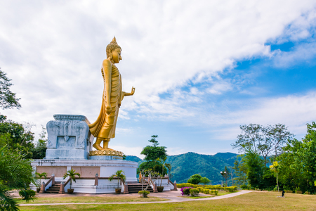 Large golden Buddha statue standing on top of mountain.