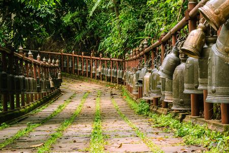 Bells hanging on rail along walking path.