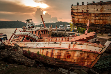 Broken and very old wooden fishing boat left abandoned on the land near the harbour. Stock Photo