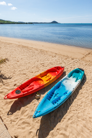 paddles: Two colorful empty canoe red and blue on the beach.