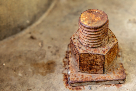 Rusty bolt and nut on concrete.