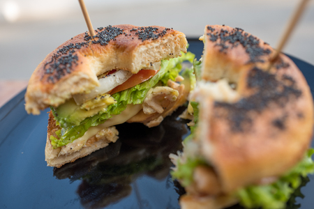 Begel black sesame with chicken salad cut in half with stick on top in black plate. Stock fotó - 126291316