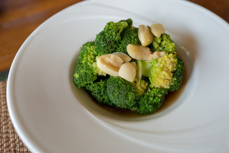 Stir fried broccoli with garlic in oyster sauce inside beautiful white round plate. Stock fotó