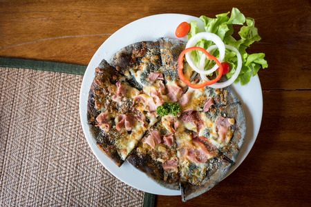 Homemade Pizza ham cheese with charcoal dough decorated with fresh vegetables on white round plate.