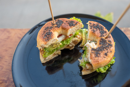 Begel black sesame with chicken salad cut in half with stick on top in black plate. Imagens