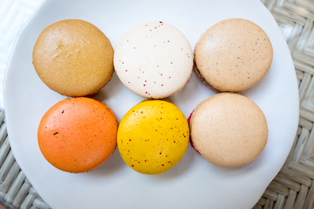 Colorful macaroon in variety taste on white round plate.