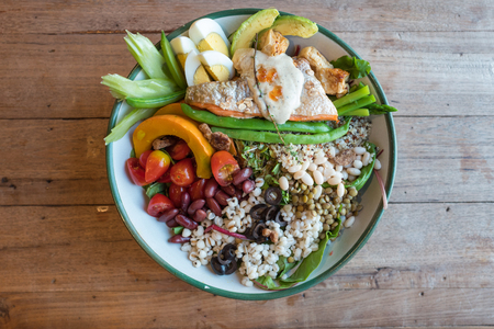 Large salad bowl of vegetables beans tomato pumpkin avocado and eggs mixed with grilled salmon on wooden table. Imagens